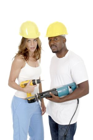 Attractive working woman and man in hardhats holding powertools looking at the camera. photo