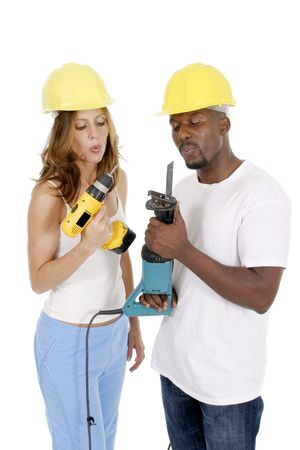 Attractive working woman and man couple in hardhats cooling their powertools by blowing on them. photo