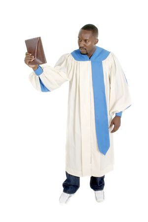 Man wearing a robe, holding a Bible, and preaching.