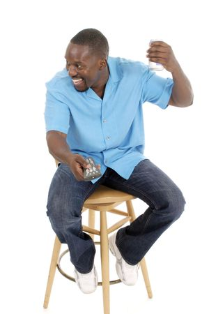 Happy smiling man sitting on a stool holding a remote control aimed forward and looking to the side while holding his favorite drink can.