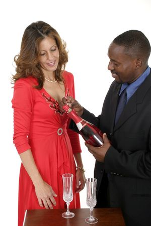 Man and woman celebrating a romantic occasion with a bottle of champagne or sparking wine.