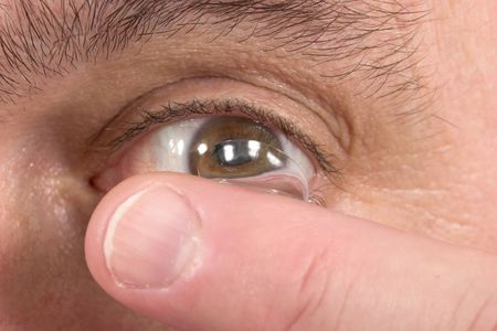 corrective: Closeup view of a mans brown eye while inserting a corrective contact lens on a finger with a white background. Stock Photo