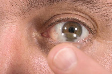 Closeup view of a man's brown eye while inserting a corrective contact lens on a finger with a white background.  Focus is on the eye and the finger and contact lens are out of focus.