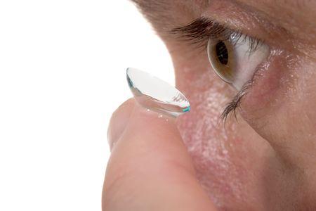 optometria: Closeup widzenia człowieka, brązowe oczy podczas wkładania naprawczych soczewek kontaktowych na palec z białym tłem. Zdjęcie Seryjne