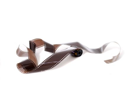 unwound: Roll of unexposed and unprocessed 35mm film and film cassette unwound.  Isolated on white background.