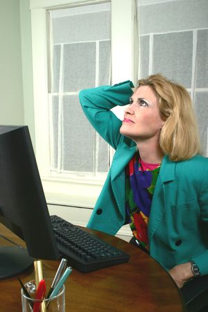 Beautiful middle aged executive business woman with her hand on her head thinking at a computer in the office.