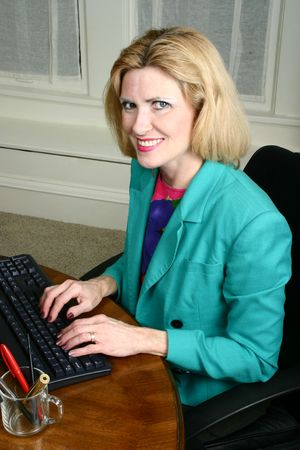 aged: Beautiful middle aged executive business woman smiling and typing on her computer keyboard in the office. Stock Photo