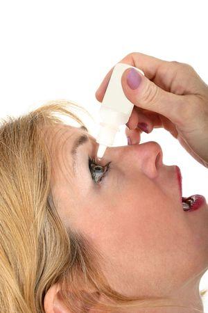 antihistamine: Closeup portrait of a beautiful middle-aged woman using eyedrops.  Shot isolated on white background. Stock Photo