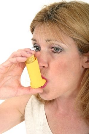 Woman demonstrates the use of an asthma or bronchial inhaler. photo