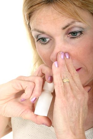 Woman demonstrates the use of an asthma or bronchial inhaler.
