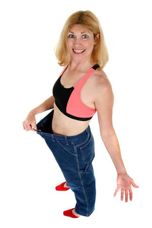 Beautiful newly slim middle aged woman demonstrates how she has lost weight by showing how an old pair of pants has room to spare. Stock Photo