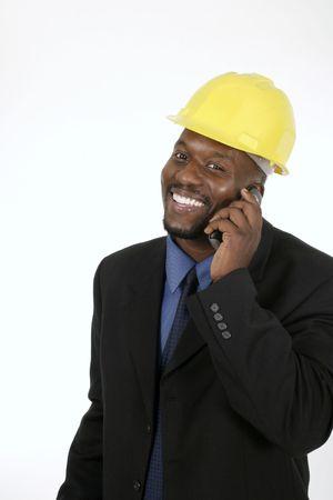Lachend architect, ingenieur, of de toezichthouder in het geel hardhat praten op een mobiel.