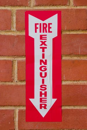 Sign pointing downward to location of a fire extinguisher on a red brick wall.