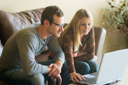 Attractive young man and woman sitting on a couch looking at a laptop computer together.  The focus is on the man closest to the computer.  The woman is slightly out of focus.