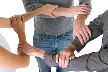 linking: Three person business team with hands and arms linked in unity and support.