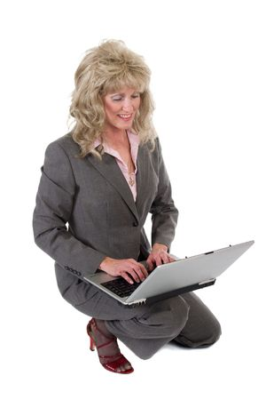 Attractive executive business woman kneeling while working on a laptop computer. photo