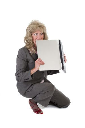 concede: Woman so frustrated with her laptop that she is trying to tear it up with her teeth Stock Photo