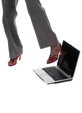 Frustrated with her laptop, this shows a womans legs and feet about to kick her laptop over. photo