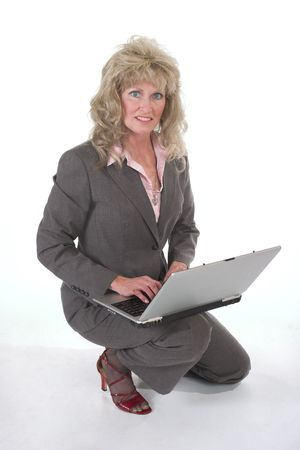 woman kneeling: Attractive executive business woman kneeling while working on a laptop computer.
