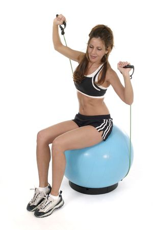 Beautiful brunette woman in a fitness workout using an exercise ball.  Shot isolated on white background. Stock Photo