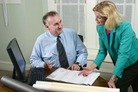 Architect showing client blueprints in the office.  Landscape horizontal orientation.