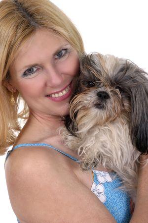 Beautiful blonde woman holding Shih Tzu dog. Stock Photo