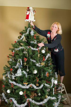 Beautiful blonde woman decorating a Christmas tree.
