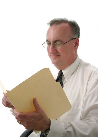 old desk: smiling business man wearing reading glasses reading report in manila folder; isolated on white background