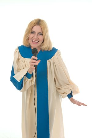 Blond woman in a choir robe holding a microphone and singing.