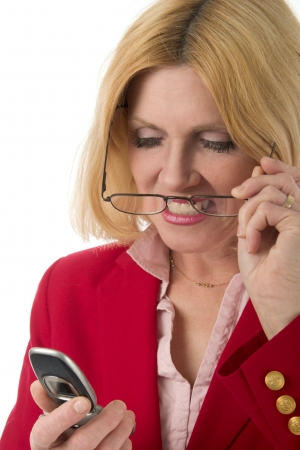 Closeup headshot of beautiful blond female executive putting on her glasses to look at cellphones caller ID. Focus is on face, cellphone is slightly out of focus.