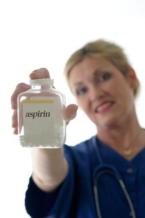 photo of nurse with stethoscope holding bottle of pills with aspirin on label in front of her; focus is on bottle of aspirin with nurse in background out of focus Stock Photo