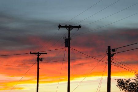 drie telefoon palen aftekenen tegen een heldere, kleurrijke hemel bij zonsondergang