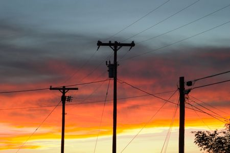 three telephone poles silhouetted against a bright, colorful sky at sunset Imagens