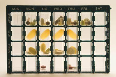 doses: Organizer voor medicatie met compartimenten voor het bijhouden van dagelijkse doses van de geneeskunde meer dan een week tijd; Organisator is rechtop, gecentreerd, vult het frame, en is verlicht van achter het maken van een aantal pillen lijken doorschijnend