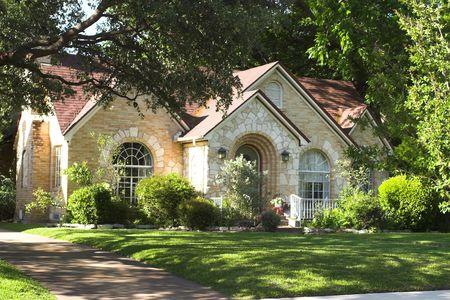 huis met een prachtige mix van licht gekleurde en witte steen en baksteen; gebogen ramen en ingang; omringd door groen gebladerte Stockfoto