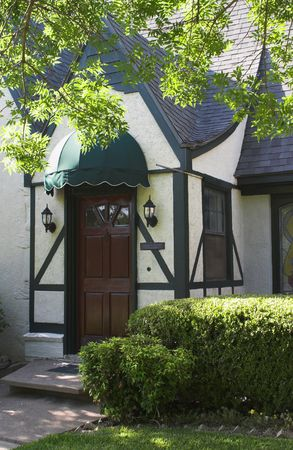 attractive entryway to tudor style house with wood door and green awning; surrounded by foliage and landscaping Stock Photo - 784268