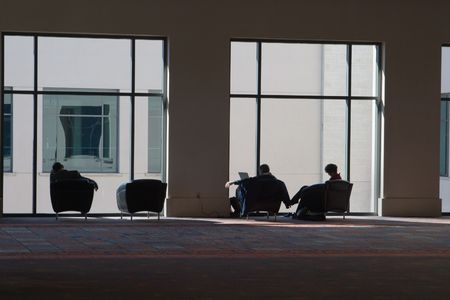 Partial silhouette of three people relaxing, reading, and listening to music in modern style comfortable chairs near a large window in a convention center. Standard-Bild