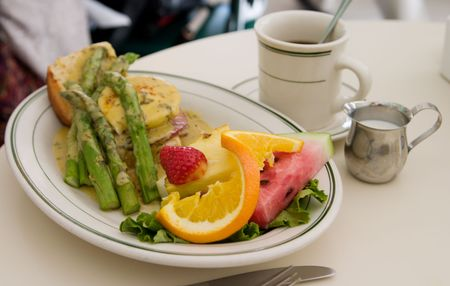 Beautiful culinary preparation of eggs benedict breakfast at a popular restaurant in a tourist area.  Focus is on the strawberry and orange slice with the rest of the scene out of focus from depth of field effect. Stock Photo - 784265