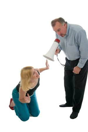 commanding: Extreme domestic argument with husband shouting commands through a megaphone at his fearful wife. Stock Photo
