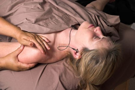 Beautiful woman listening to music on headphones and receiving relaxing massage at home photo