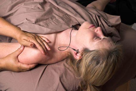 musicoterapia: Donna bella che ascolta la musica sulle cuffie e che riceve massaggio di distensione a casa