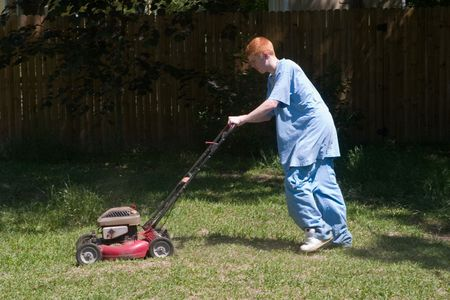 teenaged: Red-haired teenaged young man mowing the lawn on a bright summer day. Stock Photo