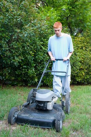 Red-haired teenaged young man mowing the lawn on a bright summer day. Stock Photo