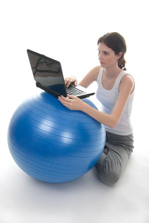 Young woman in casual clothes sitting on the floor with a laptop computer on top of an blue exercise ball used as a make-shift desk.