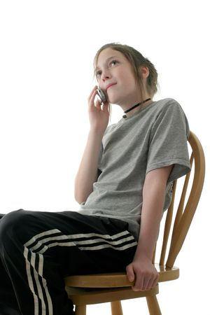 young teen girl sitting on chair and talking on cellphone; isolated on white background Stock Photo - 813033