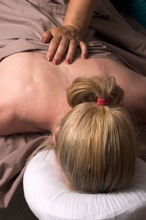 back rub: Beautiful woman receiving relaxing massage at home