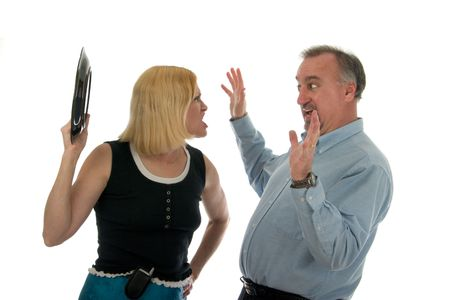 Wife shouting at, and about to hit, defensive husband with dinner plate in heated argument. Stock Photo