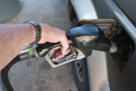 hand truck: A gasoline fuel filler held by a human hand is pumping gas into a vehicle, auto, automobile, truck, or car. Stock Photo