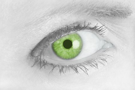 Beautiful green eye looking over toward you in faded black and white Stock Photo