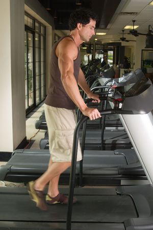 striding: Man working out on a treadmill in a fitness center.  His feet are blurred from the walking motion.